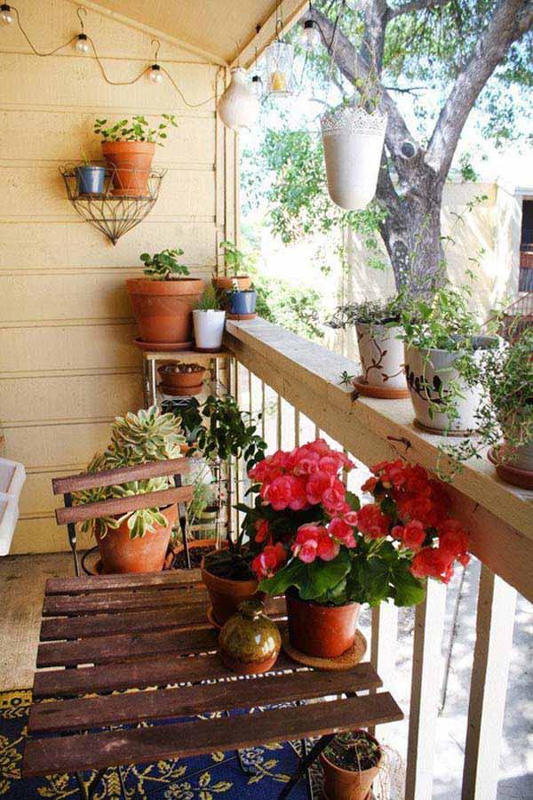 Μικρό μπαλκόνι με πολλά λουλούδια και φυτά.