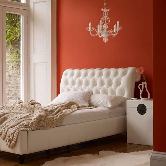 Άσπρο κρεβάτι κρεβατοκάμαρας με κόκκινους τοίχους.