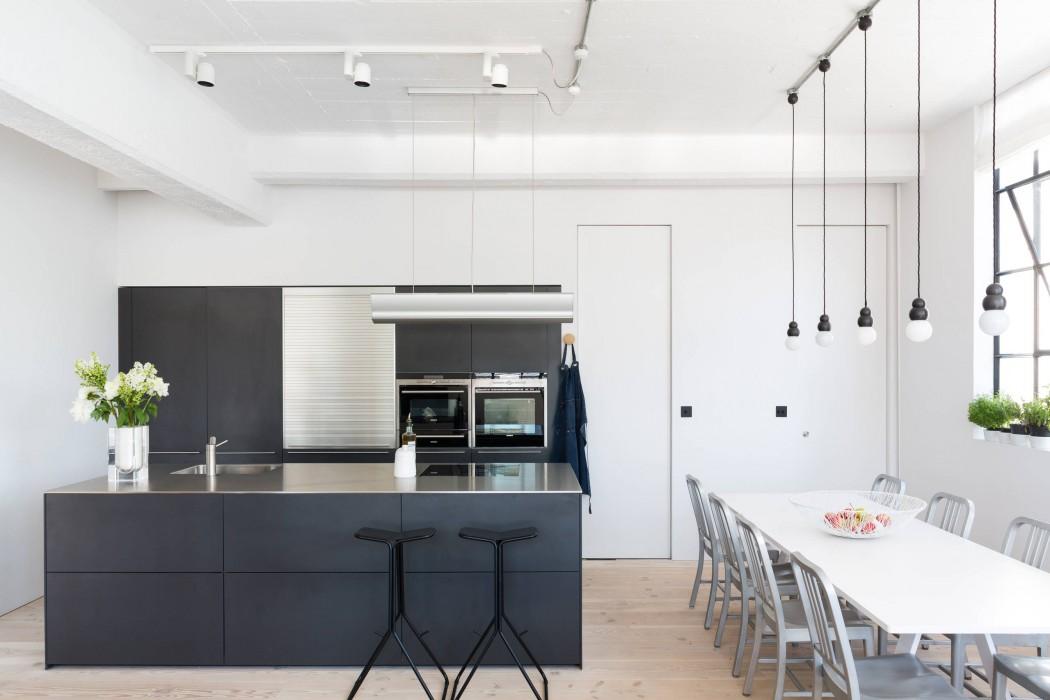 Industrial κουζίνα με μαύρους πάγκους και άσπρη τραπεζαρία.